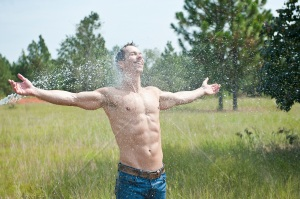 man-enjoying-being-sprayed-by-a-garden-hose-outdoors