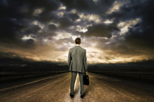Business man standing in the middle of the road. Dramatic sky ab